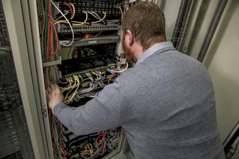 Systemingenjör jobbar i patchskåp